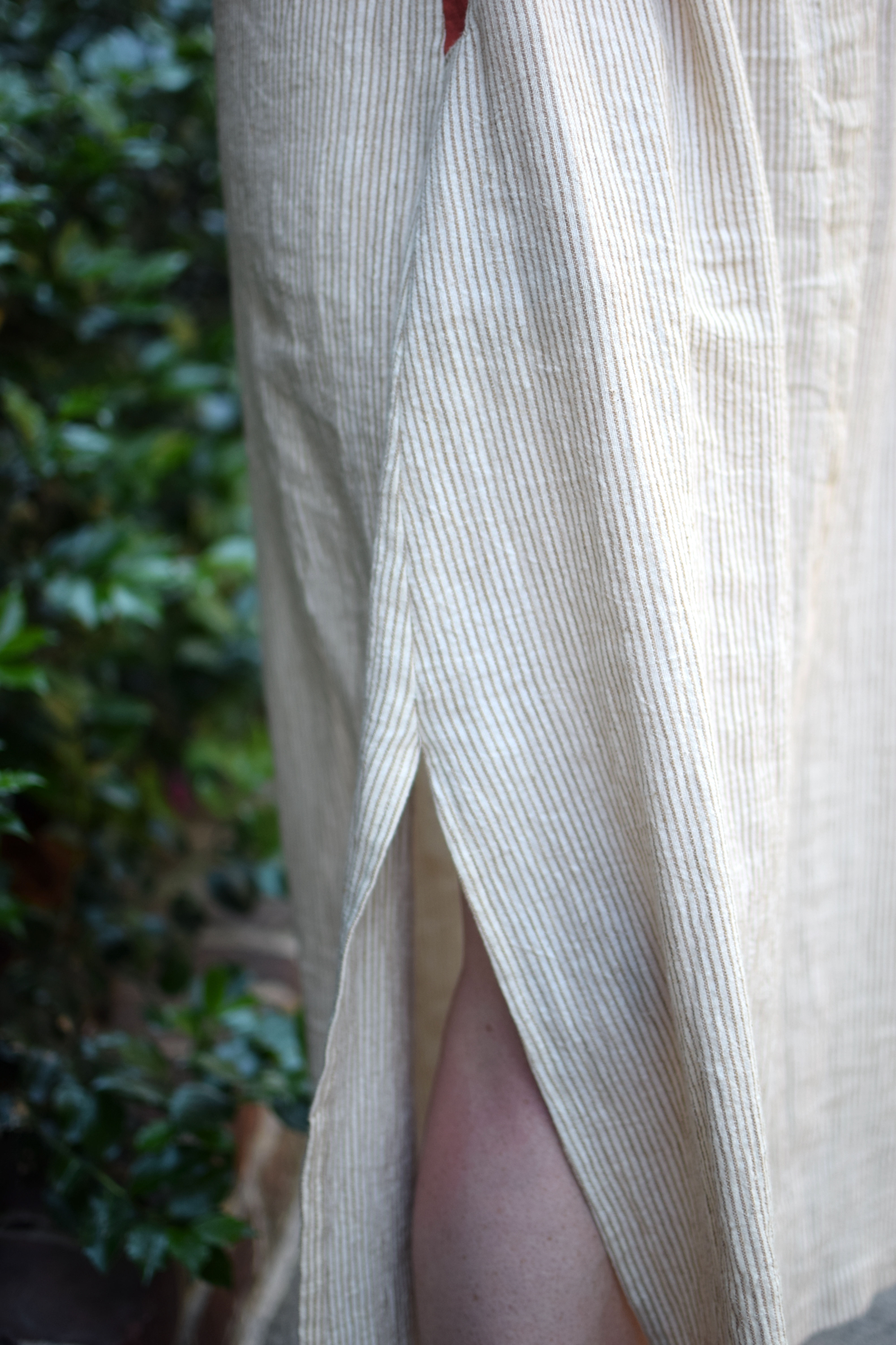 a detail view of the side slit on a brown and white striped dress.
