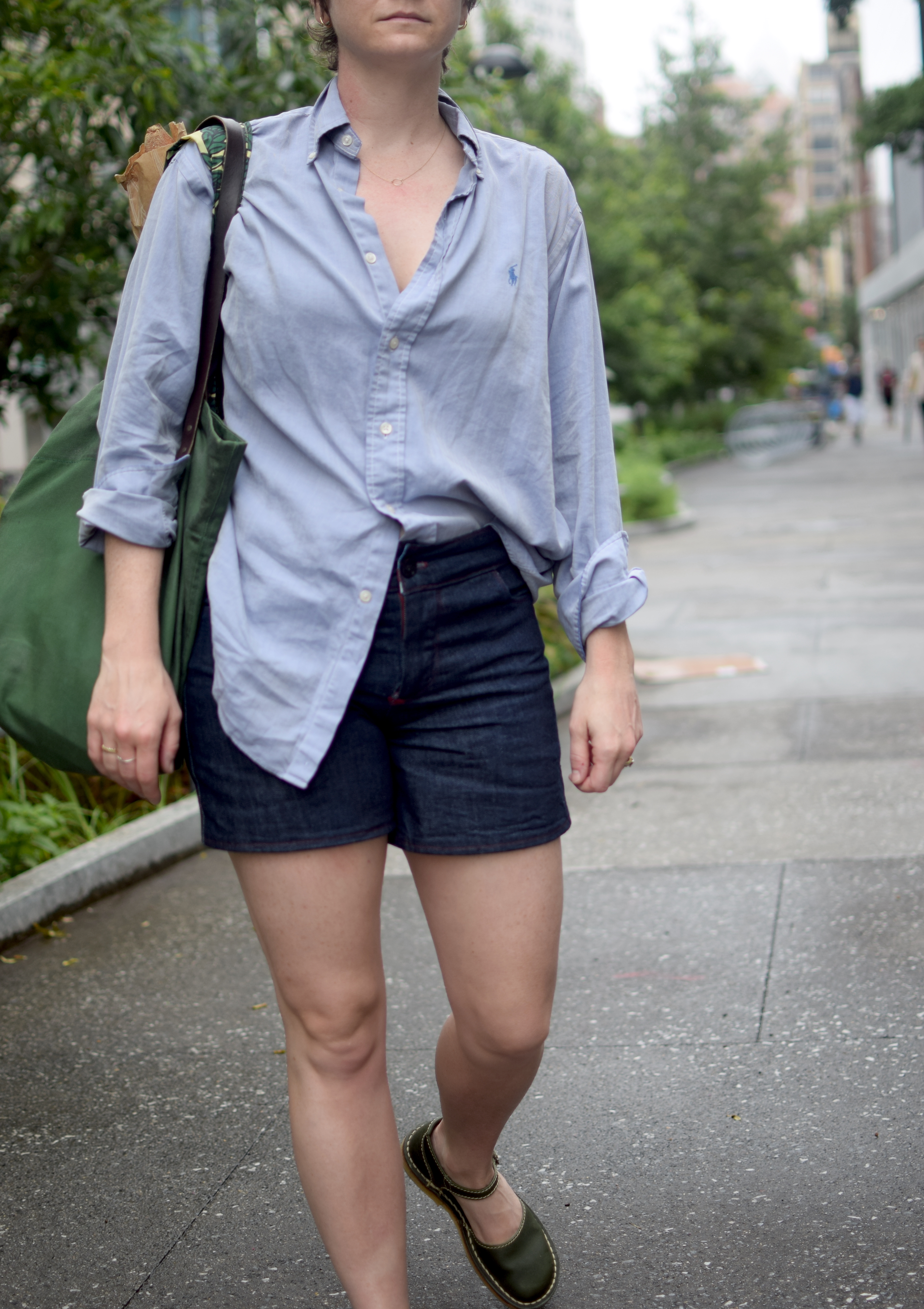 a woman poses, wearing a half-tucked button down and homemade jean shorts.