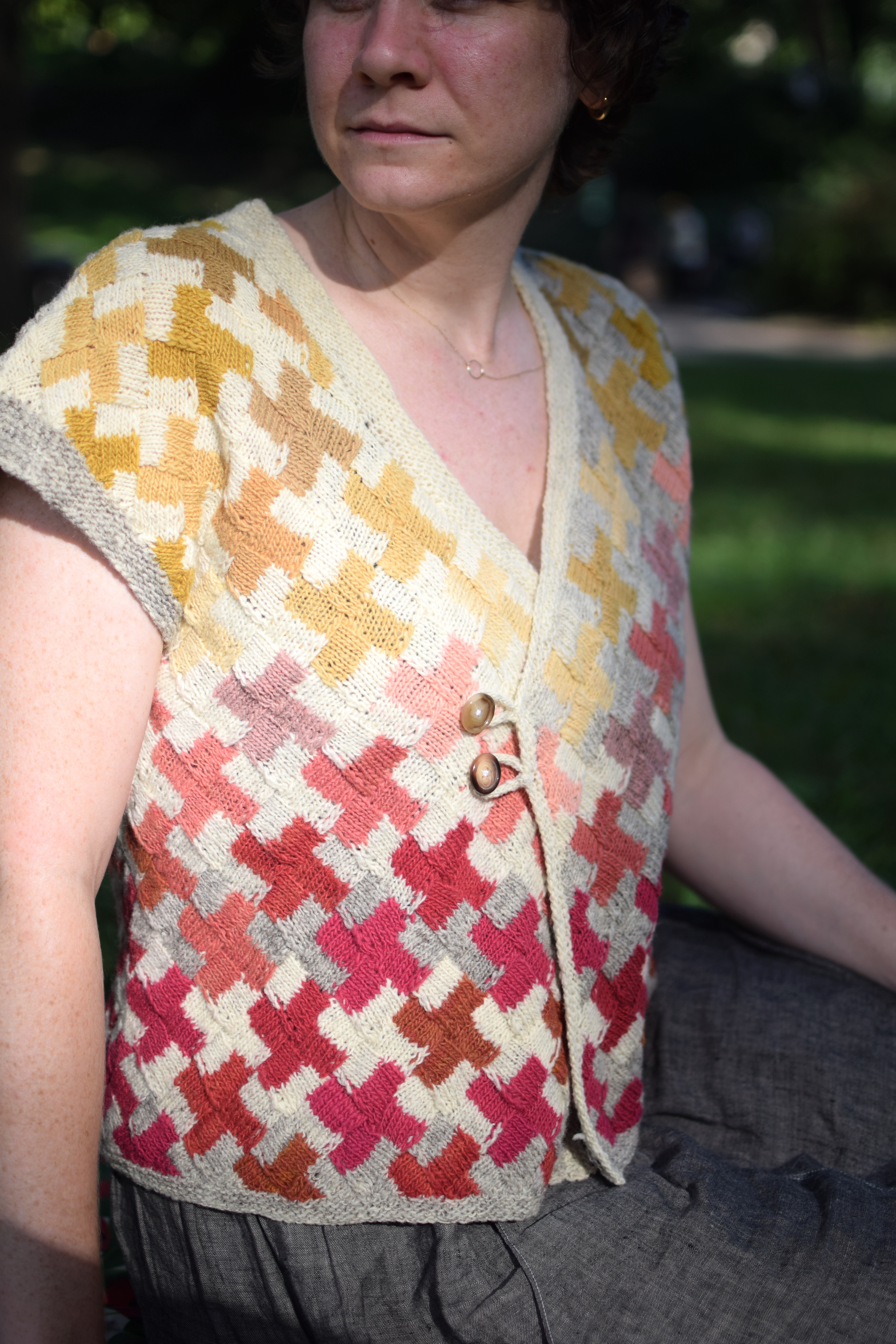 sun shines on a woman wearing a hand-knitted sweater vest.