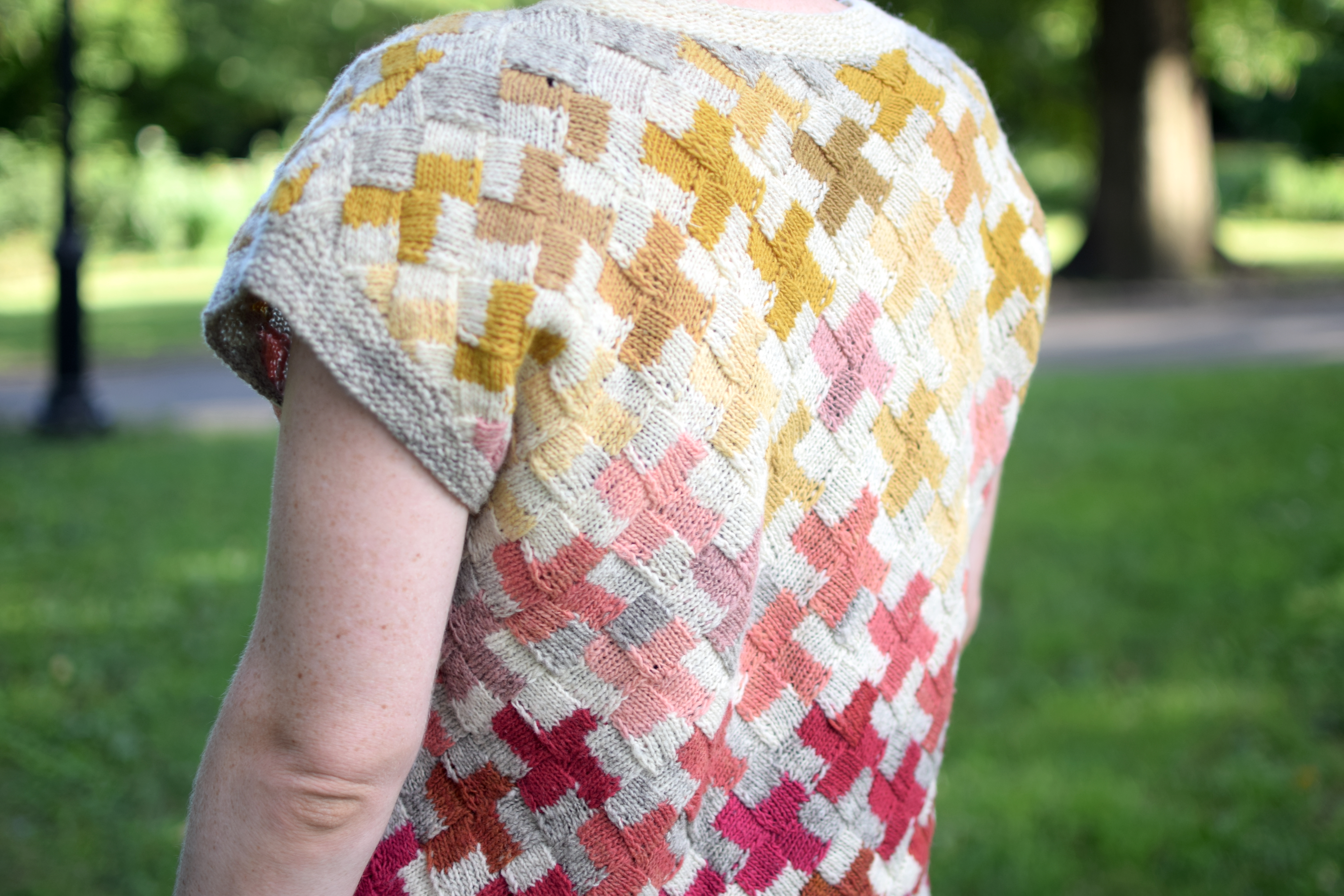 a woman wears a hand-knitted sweater in a park.