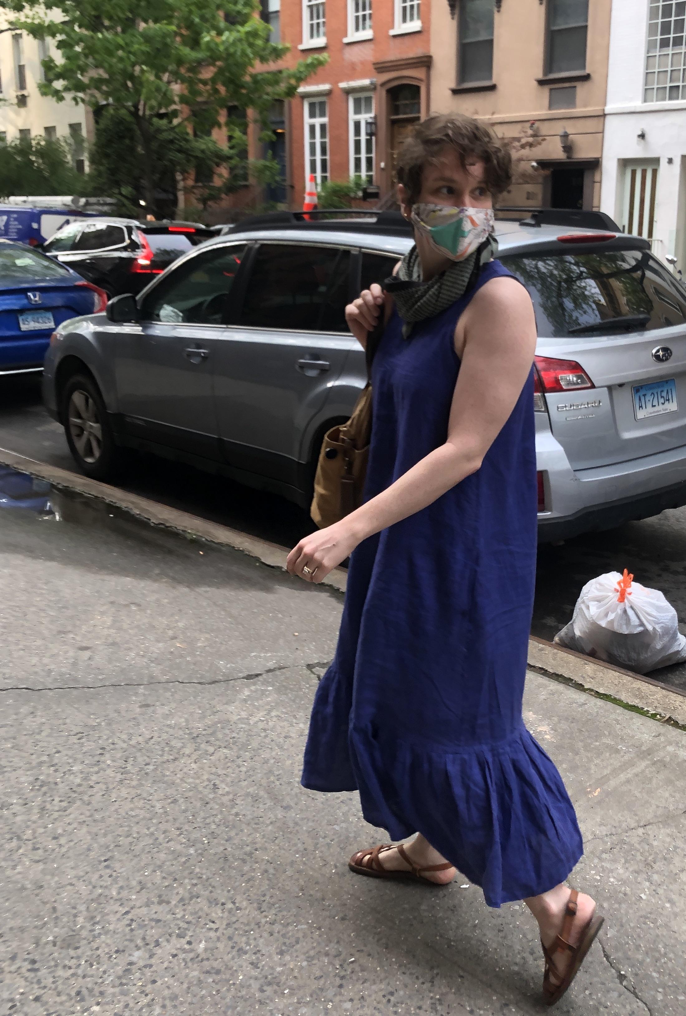 a woman walking in a New York City street, wearing a homemade blue dress